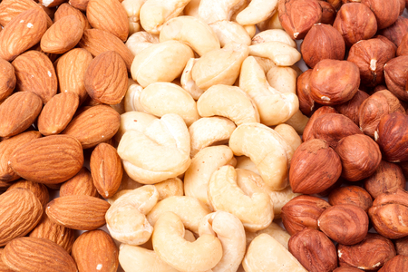 whole pecans: almonds cashews and hazelnuts peeled as background. Stock Photo