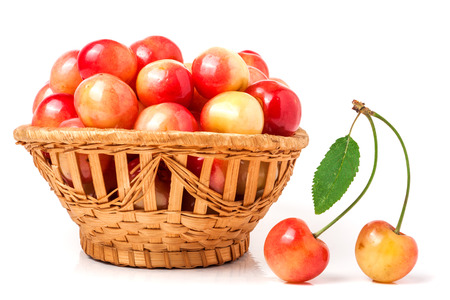 alycha: yellow cherries in a wicker basket isolated on white background.