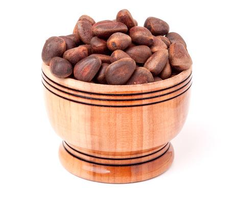 wooden barrel: unpeeled cedar nuts in a wooden barrel on a white background