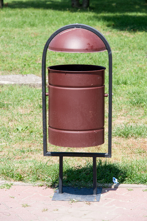 environmental sanitation: rubbish bin on the street on a background of grass.