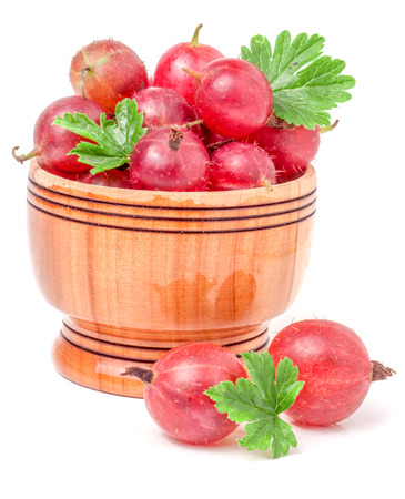 red gooseberries with leaf in a wooden bowl isolated on white background. Stock Photo