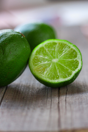 limes with half on a wooden background.