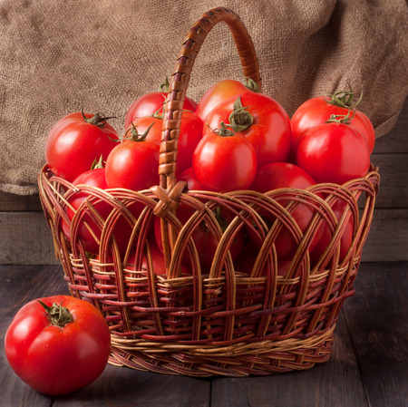 red tomatoes in a wicker basket on a dark wooden table.