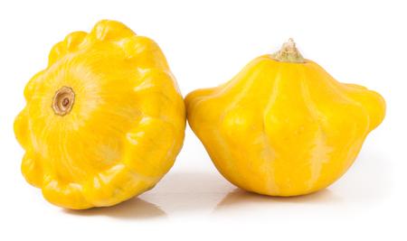 cucurbita: two yellow pattypan squash isolated on white background.