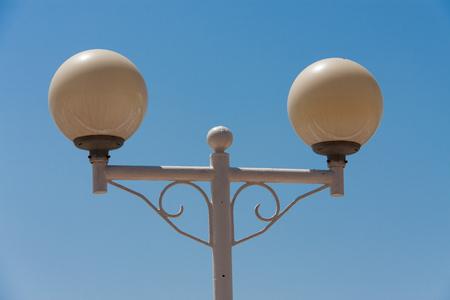 Round street lamp on blue sky background.