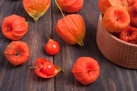 physalis scattered on a dark wooden table.