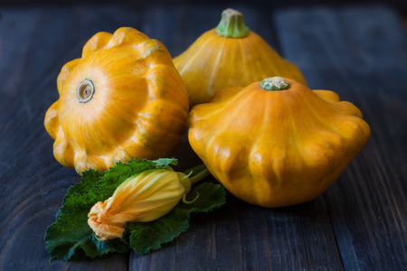 three yellow pattypan squash with leaf and flower on a dark wooden table. Stock Photo