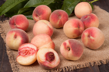 peaches in a wicker basket with leaves on wooden table. Stock Photo