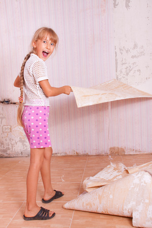 girl remove old wallpapers from the wall