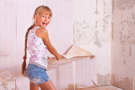 redecoration: girl remove old wallpapers from the wall