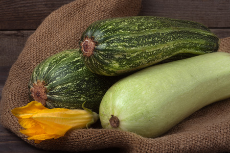 phallic: zucchini and courgette on sackcloth and wooden background with flower. Stock Photo
