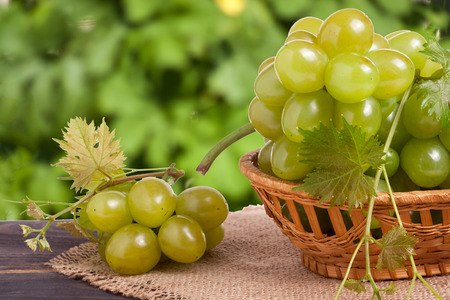 green grapes in a wicker basket on a wooden table with a blurred background. Stock Photo