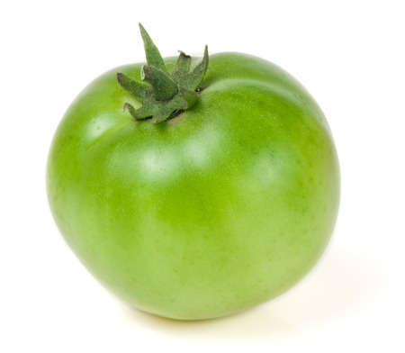 isolated on green: one green unripe tomato isolated on white background.