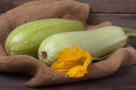 phallic: two courgettes with a flower on sackcloth and wooden background. Stock Photo