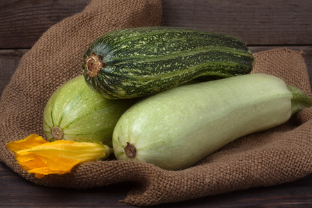 phallic: green zucchini and courgettes with a flower on sackcloth and wooden background.