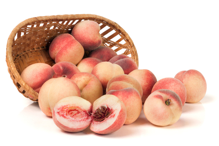 peaches in a wicker basket isolated on white background.