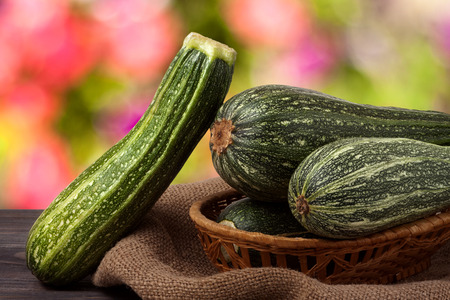 phallic: green zucchini on the wooden table with sacking and a blurred background. Stock Photo