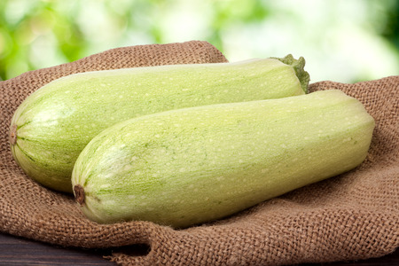 courgettes: two courgettes on sackcloth with a blurred background. Stock Photo