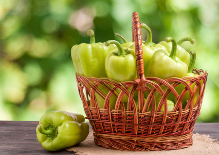 green bell peppers in a wicker basket on a wooden table with a blurred background.