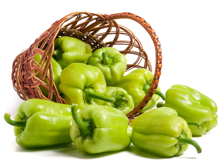 green bell peppers in a wicker basket isolated on white background.