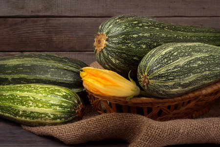 phallic: green zucchini or courgettes with a flower on sackcloth wooden background.