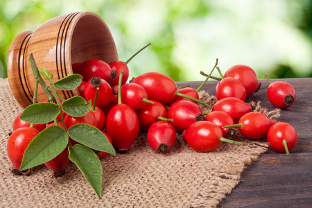 Fresh rosehip berries in a wooden bowl on the board with a burlap and a blurred background Stok Fotoğraf