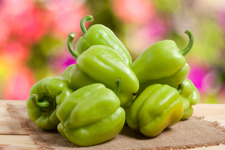 pile green pepper on a wooden table with a blurred background.