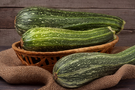 medula: green zucchini or courgettes on sackcloth wooden background.