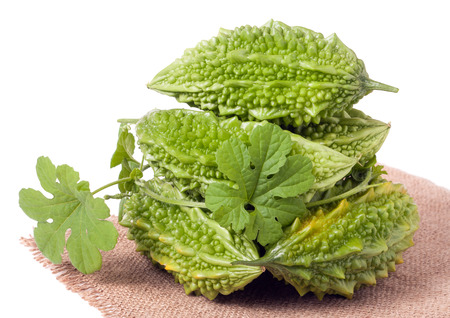 heap of bitter melon or momordica with leaves isolated on white background.