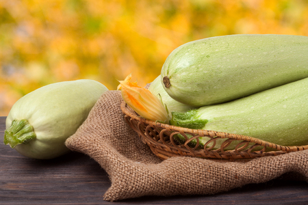 courgettes: three courgettes with a flower on sackcloth and wooden background.