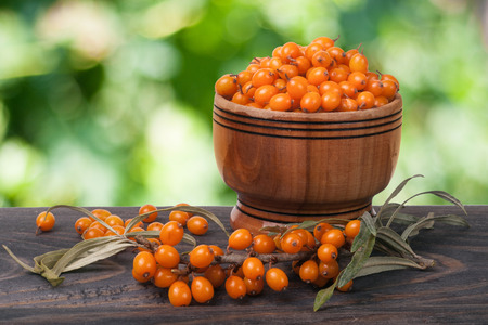 argousier: Sea-buckthorn berries in a wooden bowl on a table with blurred garden background.
