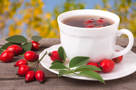 cup of tea rosehip berries on a dark wooden background. Banco de Imagens