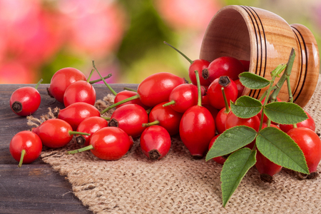 Fresh rosehip berries in a wooden bowl on the board with a burlap and a blurred background Stock Photo