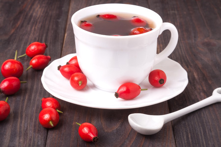 cup with rose hip tea on a dark wooden background. Banco de Imagens