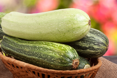 courgettes: green zucchini and courgettes on sackcloth with a blurred background.