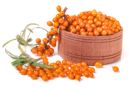 Sea-buckthorn berries in a wooden bowl with a sprig isolated on white background.