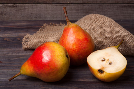 two and a half: two pears with half on a dark wooden background.
