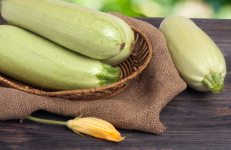 phallic: three courgettes with a flower on sackcloth and wooden background.