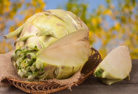 fresh cabbage kohlrabi in a wicker bowl on a dark wooden table with a blurred background. Stock Photo