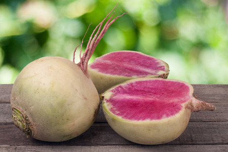 One whole and sliced watermelon radish on a wooden table with blurred garden background.