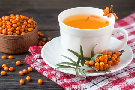 seabuckthorn: Tea of sea-buckthorn berries with branch on dark wooden background.