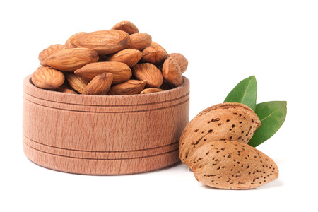 heap of almonds in their skins and peeled with leaf isolated on white background. Stock Photo
