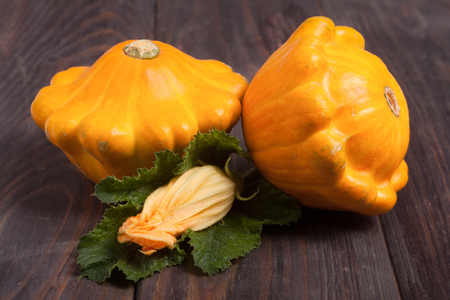 two yellow pattypan squash with leaf and flower on a dark wooden table.
