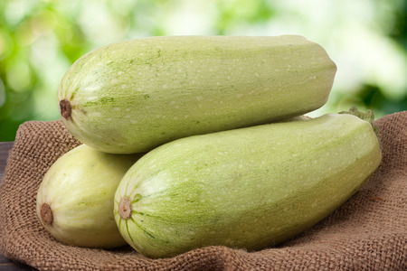 courgettes: three courgettes on sackcloth with a blurred background.