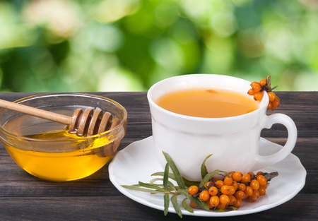 Tea of sea-buckthorn berries with honey on wooden table with blurred garden background. Stock Photo