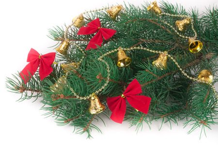 branch of Christmas tree with short needles decorated bells and bows isolated on white background. Stock Photo