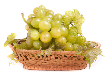 green grapes in a wicker basket isolated on white background. Stock Photo