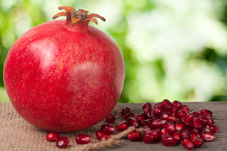 One pomegranate on the old wooden board with blurred garden background. Stock Photo