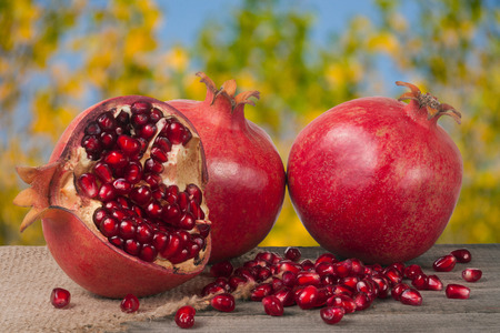 two and a half: two whole pomegranate and a half on the old wooden board with blurred garden background.