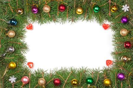 Christmas frame made of fir branches decorated with balls isolated on white background.